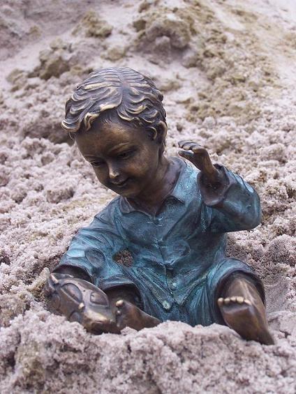 Kleiner Junge spielt mit Spielzeugauto als Bronzeskulptur