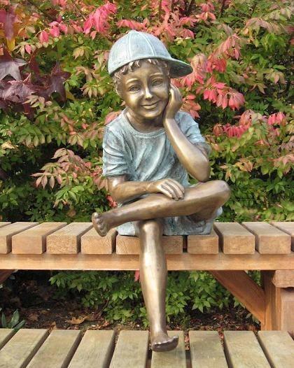 Junge mit Cappy sitzend als Bronzeskulptur
