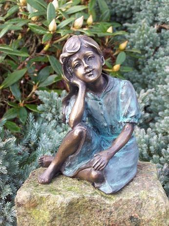 Mädchen Lisa stützt sich auf Knie ab als Bronzeskulptur