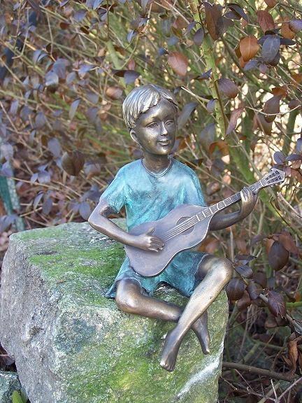 Der Junge Benjamin spielt Gitarre als Bronzeskulptur