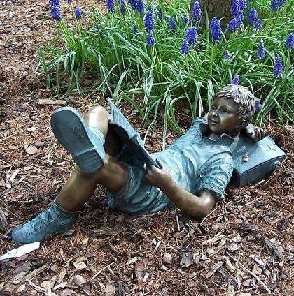 Junge Andrew liest Buch liegend als Bronzeskulptur