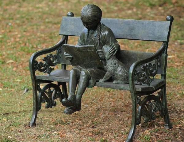 Julia auf Gartenbank mit Buch und Welpen als Bronzeskulptur