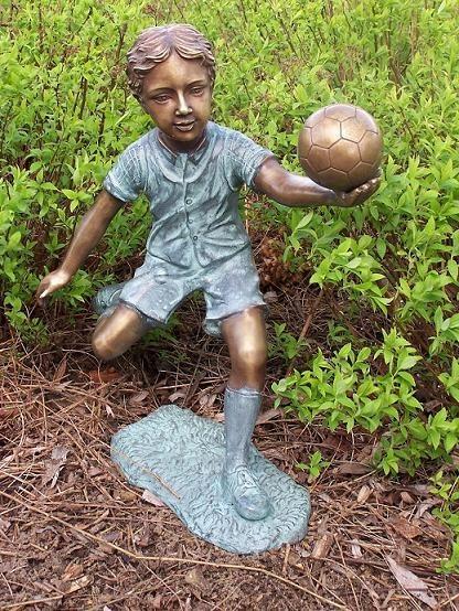 Junge Liam spielt Ball als Bronzeskulptur