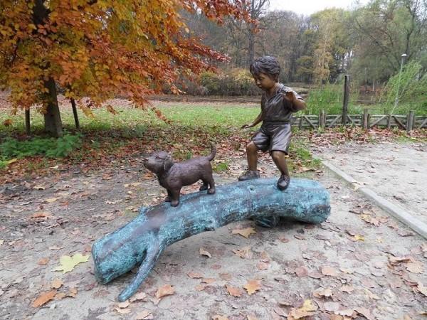 Kleiner Junge balanciert mit Hund auf einem Baumstamm als Bronzeskulptur