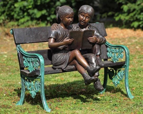 Mädchen Luisa mit Freund beim Buch lesen auf einer Gartenbank als Bronzeskulptur