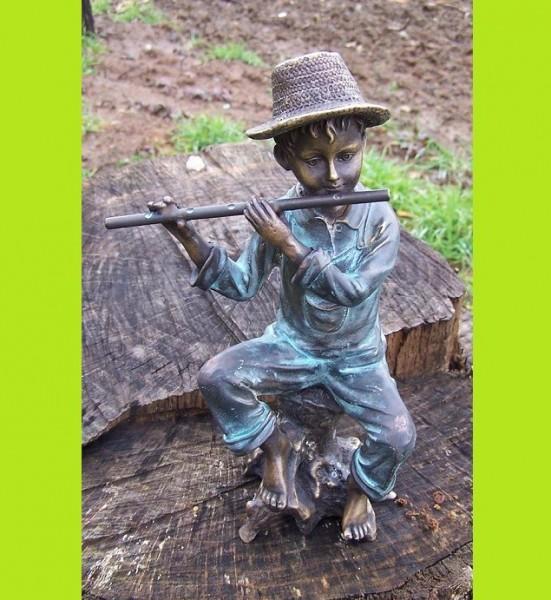 Der Junge Tim spielt Flöte sitzend auf einem Baumstamm als Bronzeskulptur