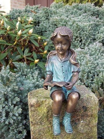 Mädchen Ines mit Zöpfen liest ein Buch als Bronzeskulptur