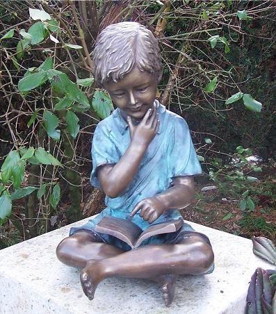 Kleiner Junge Simon liest ein Buch als Bronzeskulptur