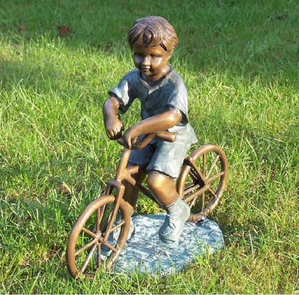 Kleiner Junge auf seinem Fahrrad als Bronzeskulptur