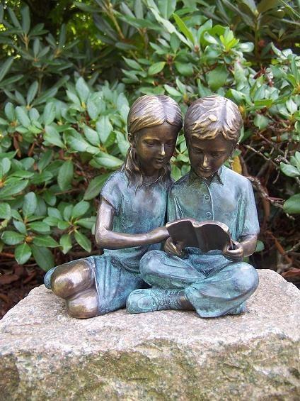 Das Geschwisterpaar Claudia und Stefan lesen ein Buch gemeinsam als Bronzeskulptur