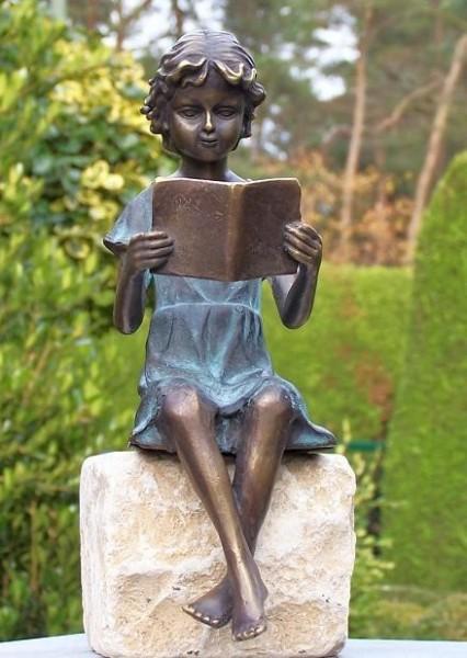Mädchen Linda in Kleid mit Patina sitzend liest Buch als Bronzeskulptur