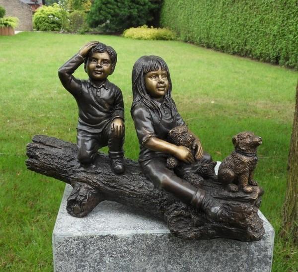 Junge und Mädchen auf Baumstamm als Bronzeskulptur